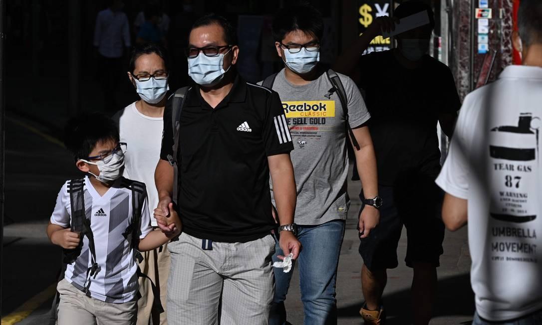 Moradores de máscara passeiam por Hong Kong: com aumento de casos, governo local anunciou medidas para conter novo surto de coronavírus Foto: ANTHONY WALLACE / AFP