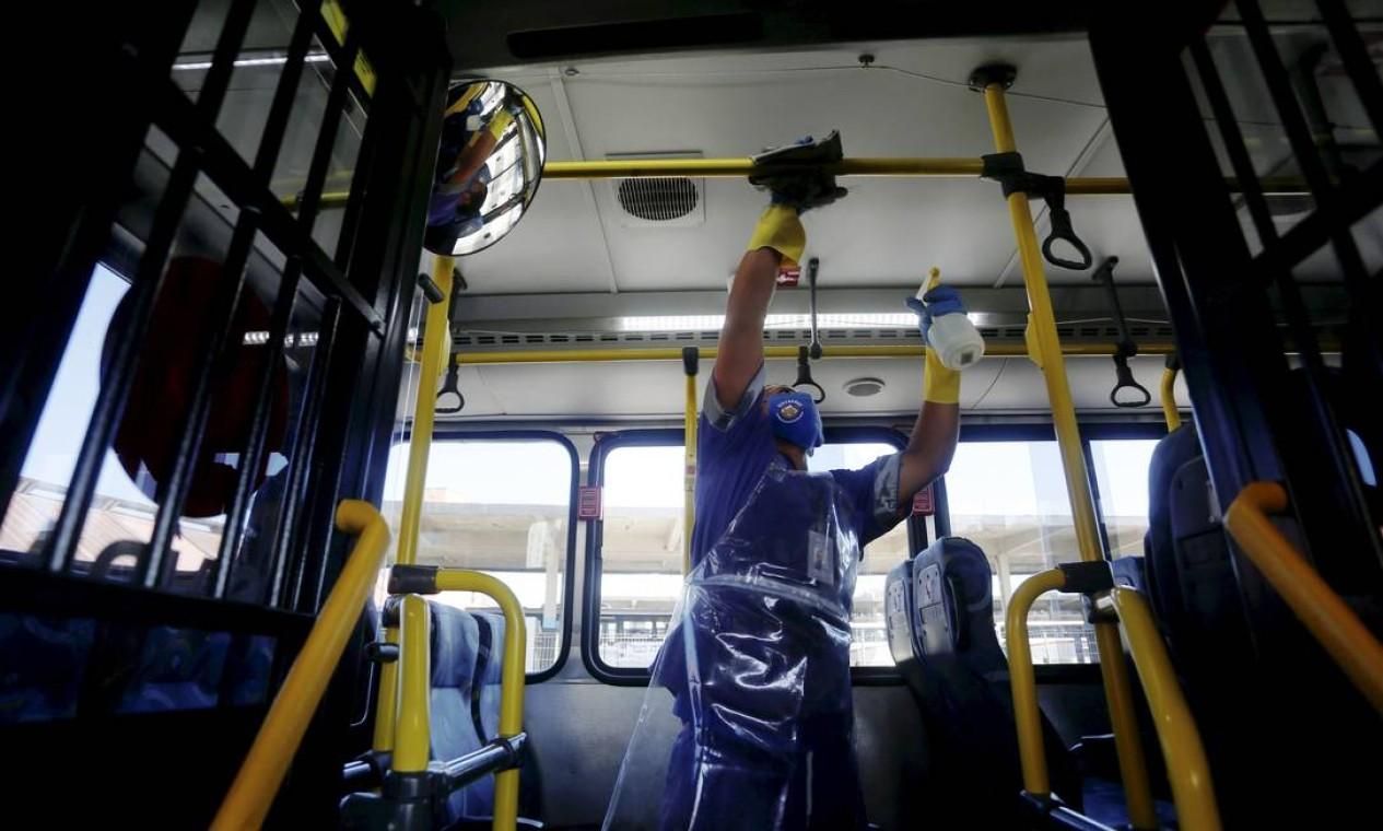 Funcionário limpa corrimãos de ônibus no terminal, antes de sair para nova viagem Foto: Fabiano Rocha / Agência O Globo