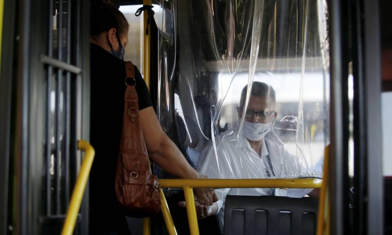 Apesar do cuidado, o motorista continua recebendo dinheiro dos passageiros Foto: Fabiano Rocha / Agência O Globo