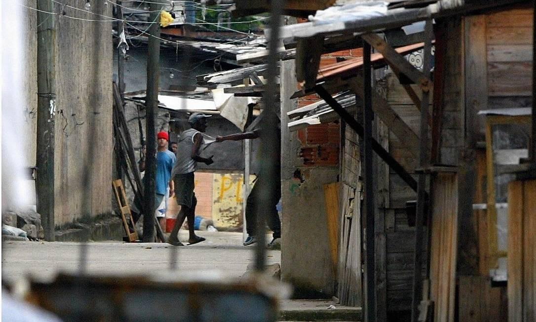 Traficante armado dentro da favela Mandela 1 tira morador do meio de tiroteio. Prêmio IBCCRIM em 2004 Foto: Michel Filho / Agência O Globo