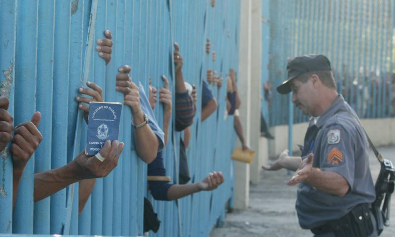 Cerca de 20 mil pessoas enfrentam até a polícia por uma vaga de gari, no Sambódromo do Rio. Tentativa de conseguir um emprego acabou em tumulto e bombas de efeito moral lançadas pelo Batalhão de Choque da PM. Prêmio Rey de Espanha 2003 Foto: Domingos Peixoto / Agência O Globo