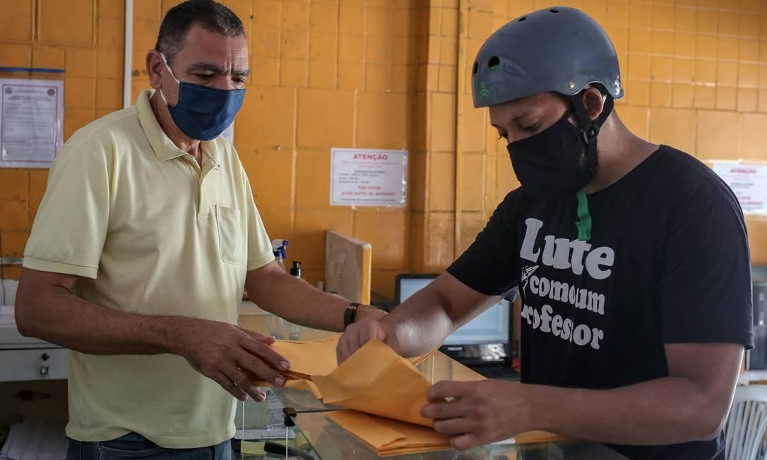 Arthur Cabral verifica as cópias impressas dos livros escolares antes entregá-los aos seus alunos que residem em bairro pobre de Camaragibe, município do estado de Pernambuco Foto: LEO MALAFAIA / AFP