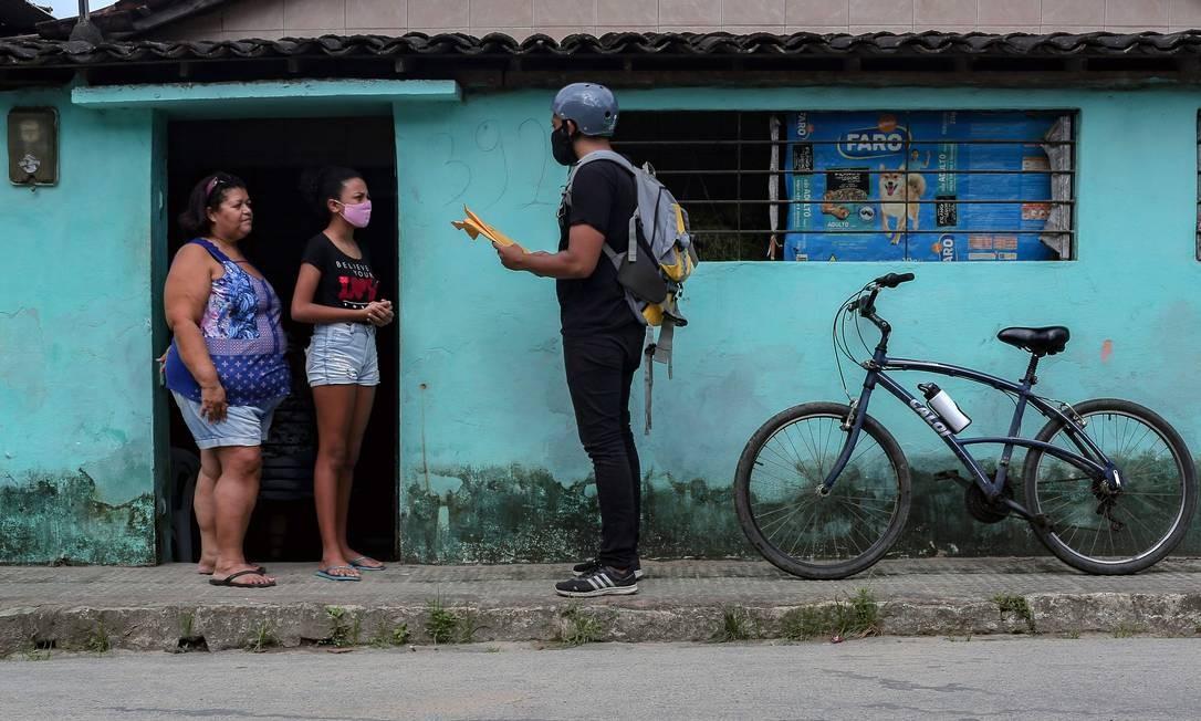 Arthur entrega versão impressa de livro didático para a estudante Suemily Alves, 11 anos Foto: LEO MALAFAIA / AFP