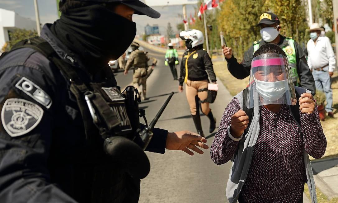 Policial para Celia Capira Mamani, que corria atrás do carro do presidente Martin Vizcarra durante uma visita em Arequipa. Seu marido morreu de coronavírus dias depois e vídeo viralizou Foto: DENIS MAYHUA / AFP