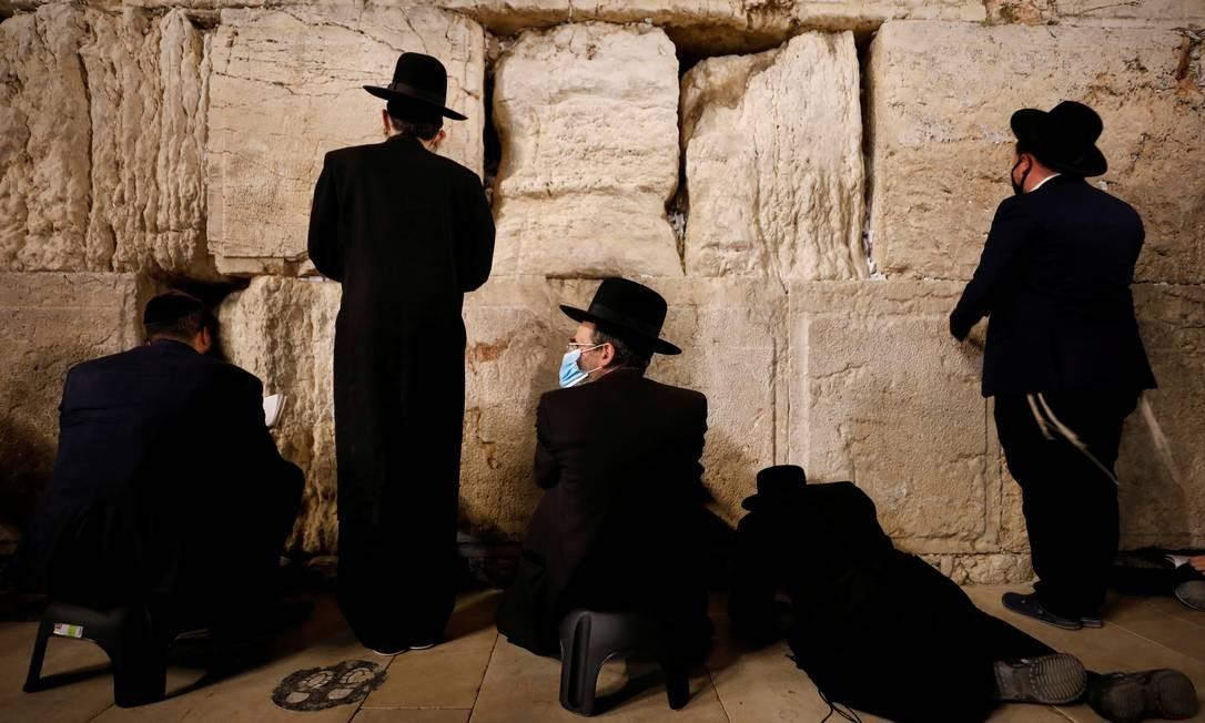 Judeus rezam em Tisha B'Av, no Muro das Lamentações, na cidade velha de Jerusalém, durante dia de jejum e lamento, para celebrar a data do calendário judaico em que se acredita que o Primeiro e o Segundo Templos foram destruídos Foto: AMIR COHEN / REUTERS