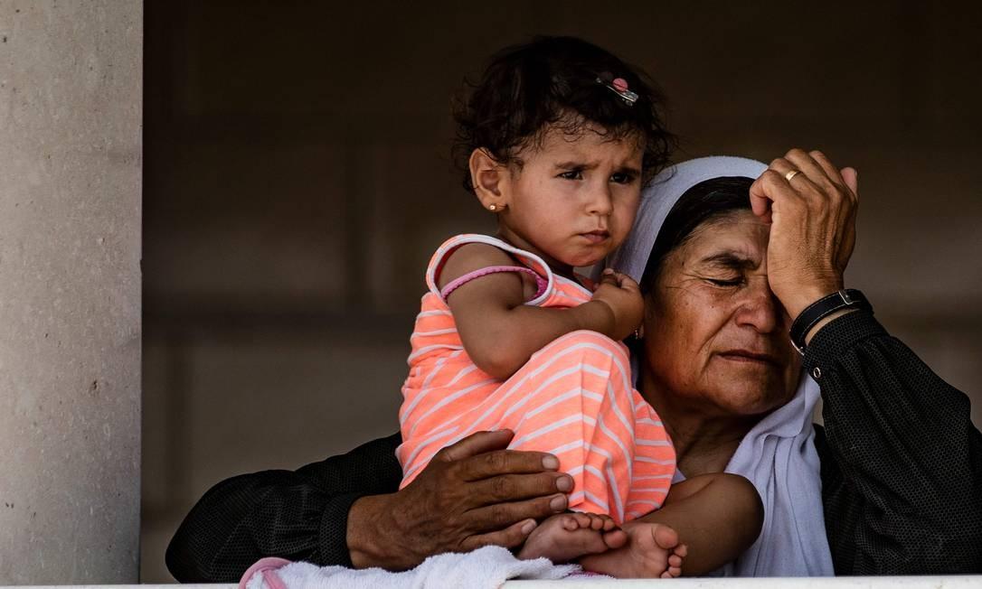 Mulher síria, que ficou presa após o fechamento da fronteira devido a uma pandemia, espera com uma criança para atravessar o Curdistão iraquiano, a partir do lado sírio da passagem da fronteira de Semalka, no nordeste da Síria Foto: DELIL SOULEIMAN / AFP