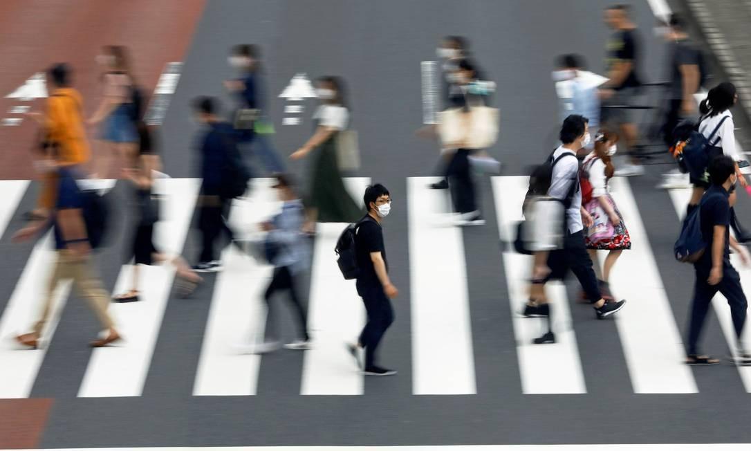 Homem usando uma máscara protetora que atravessa uma rua em Tóquio. A curva de novos casos no Japão voltou a apresentar uma curva acentuada, desde meados de junho – superando a última aceleração que aconteceu em abril Foto: ISSEI KATO / REUTERS