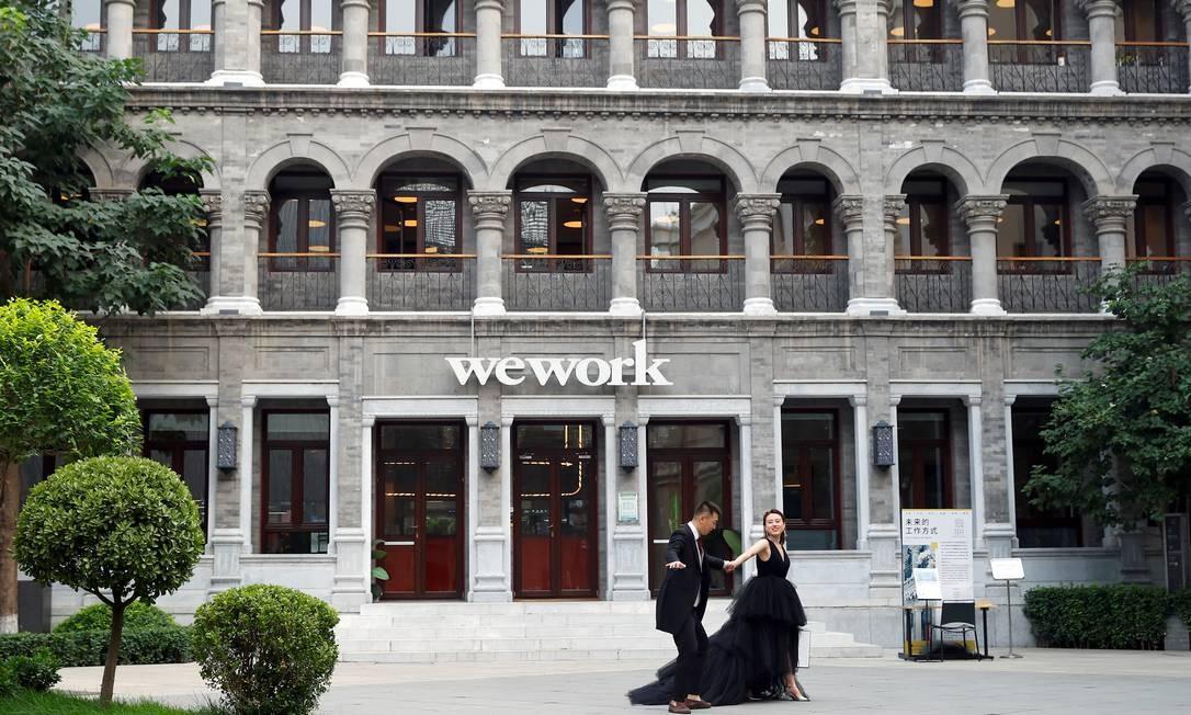 Casal posa para uma sessão de fotos em frente a uma saída do WeWork, em uma parte histórica de Pequim, na China Foto: THOMAS PETER / REUTERS