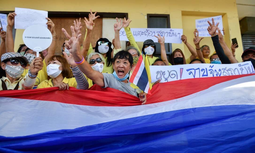 Pró-monarquistas, vestindo camisas amarelas, agitam uma bandeira nacional tailandesa em apoio à monarquia e ao governo do primeiro-ministro Prayuth Chan-ocha, no Monumento à Democracia em Bangcoc, Tailândia. Prayuth é um general do exército que deu um golpe militar no país em 2014 e tem enfrentado protestos pedindo a sua saída Foto: CHALINEE THIRASUPA / REUTERS