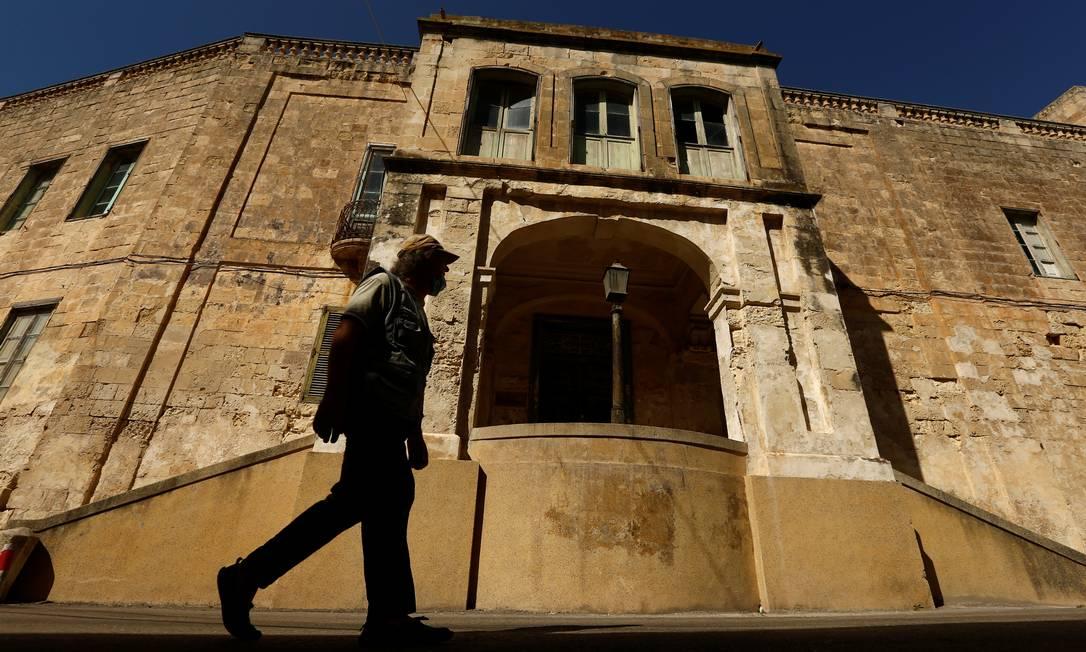 Homem passa pela entrada principal da Villa Guardamangia, nome da antiga residência da rainha Elizabeth e do príncipe Philip da Grã-Bretanha, em Pieta, Malta Foto: DARRIN ZAMMIT LUPI / REUTERS