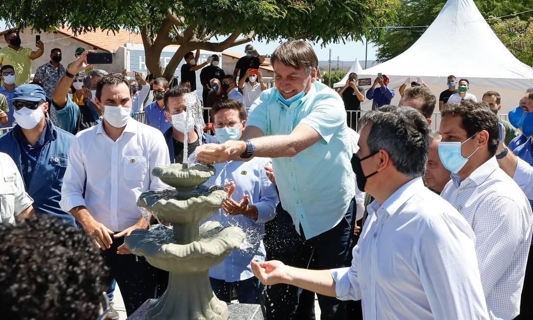 O presidente Jair Bolsonaro aciona fonte conectada ao sistema de abastecimento de água de Campo Alegre de Lourdes (BA) Foto: Isac Nobrega/PR / Agência O Globo