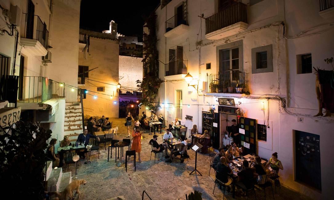 Pessoas estão sentadas em um bar na rua de la Virgen, em Ibiza; Espanha entra em recessão após queda histórica de 18,5% do PIB por conta da pandemia do coronavírus Foto: Jaime Reina / AFP