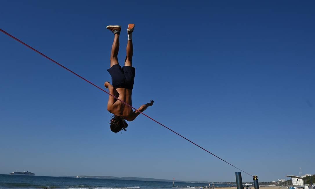 Sandor Nagy pratica slackline na praia de Boscombe em Bournemouth, sul da Inglaterra Foto: GLYN KIRK / AFP