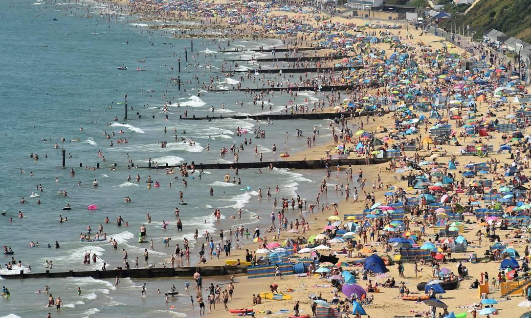 """Os banhistas apreciam o sol na praia de Bournemouth, em Bournemouth, sul da Inglaterra, que enfrenta um """"calourão"""" de 26 graus Foto: GLYN KIRK / AFP"""
