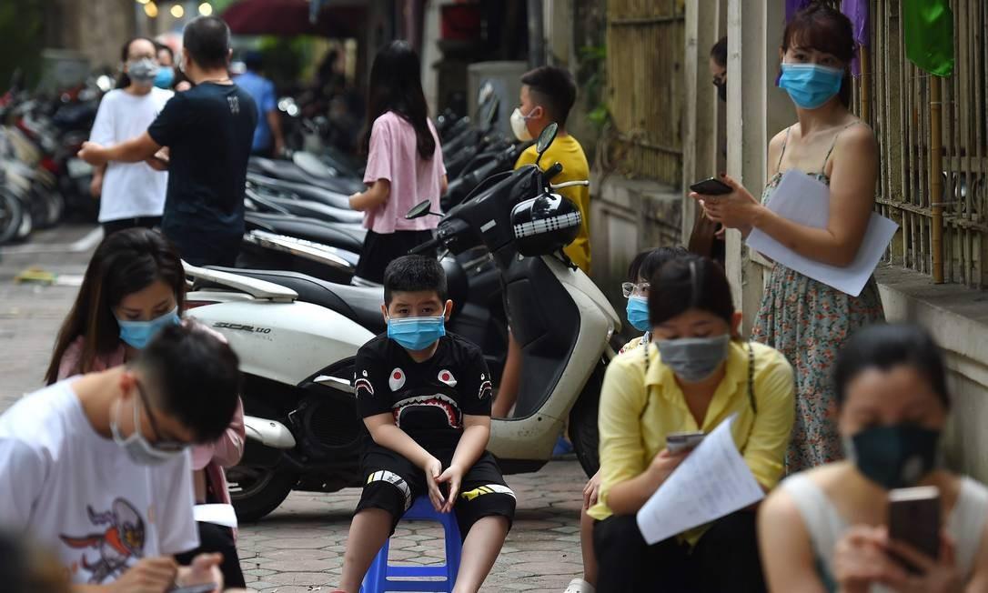 Cidadãos da capital Hanói, no Vietnã, aguardam para fazer o teste da Covid-19 Foto: Nhac Nguyen / AFP