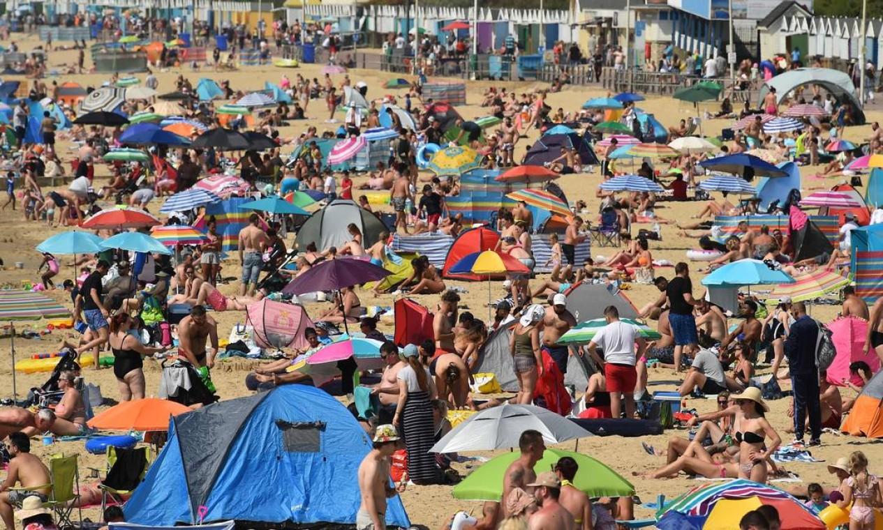 Banhistas apreciam o sol enquanto tomam sol e brincam no mar na praia de Bournemouth, sul da Inglaterra Foto: GLYN KIRK / AFP