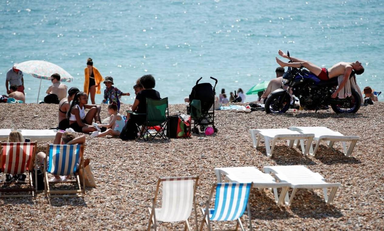 Um homem toma banho de sol deitado em uma moto, enquanto as pessoas aproveitam o clima ensolarado em uma praia em Brighton, Inglaterra Foto: PAUL CHILDS / REUTERS