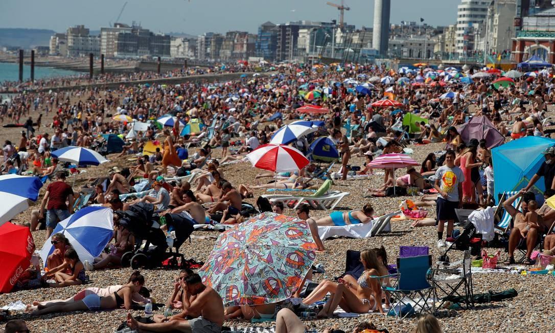As pessoas desfrutam do clima ensolarado em uma praia em Brighton, Grã-Bretanha. A partir de amanhã a temperatura volta a cair e a semana será com máxima de 22 graus Foto: PAUL CHILDS / REUTERS