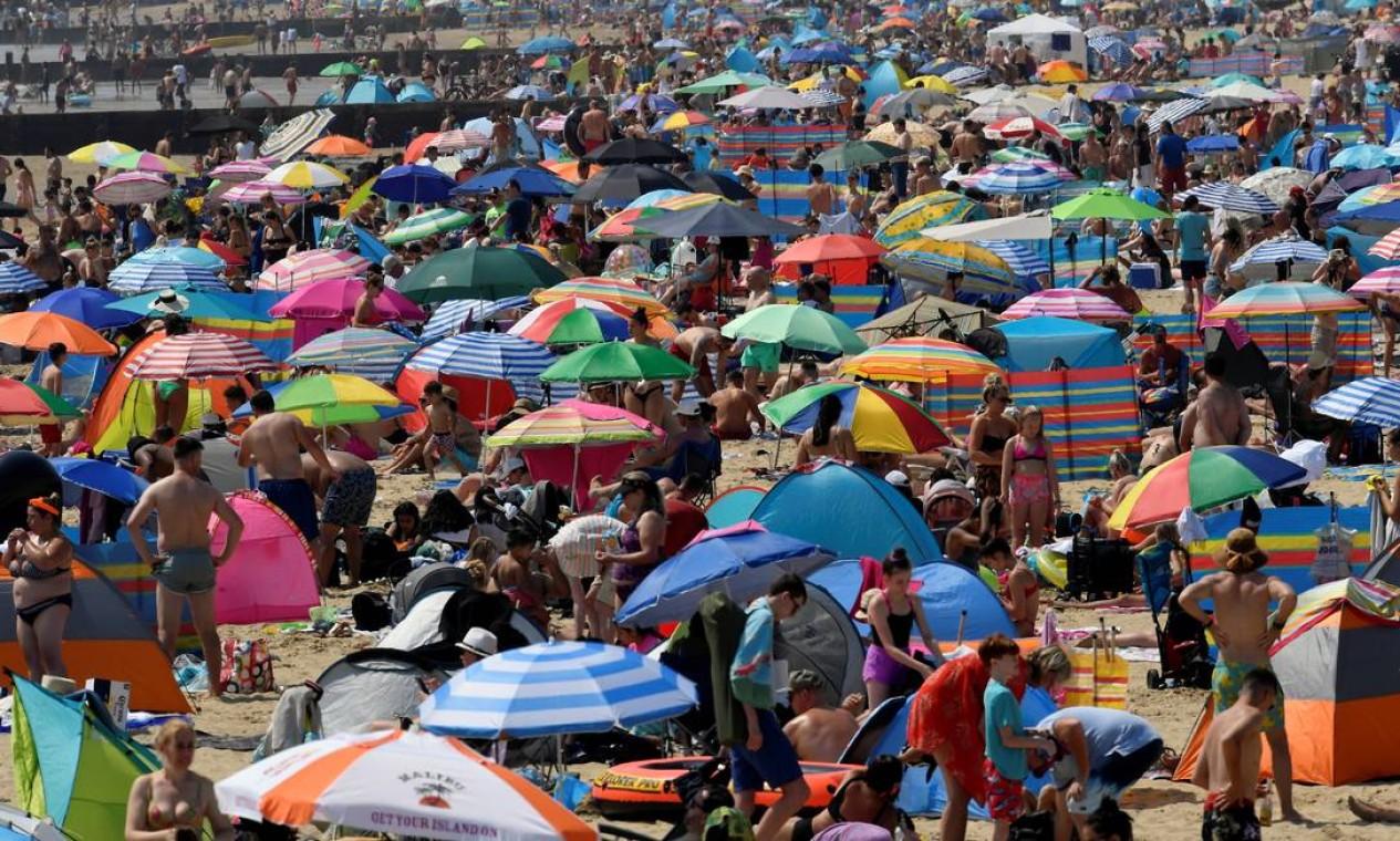 Praia em Bournemouth ficou lotada com onda de calor que atingiu a Inglaterra nos úlitmos. A partir deste sábado, a temperatura cai, com o sol aparecendo entre nuvens. O tempo volta a ficar ensolarado na próxima sexta-feira Foto: TOBY MELVILLE / REUTERS