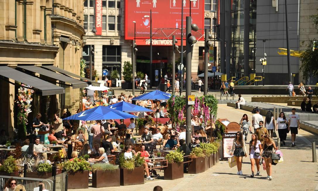 As pessoas andam pelos restaurantes e cafés perto de The Printworks, no centro de Manchester, no noroeste da Inglaterra, onde o governo suspendeu as medidas de flexibilização, devido a pico de novos casos Foto: OLI SCARFF / AFP