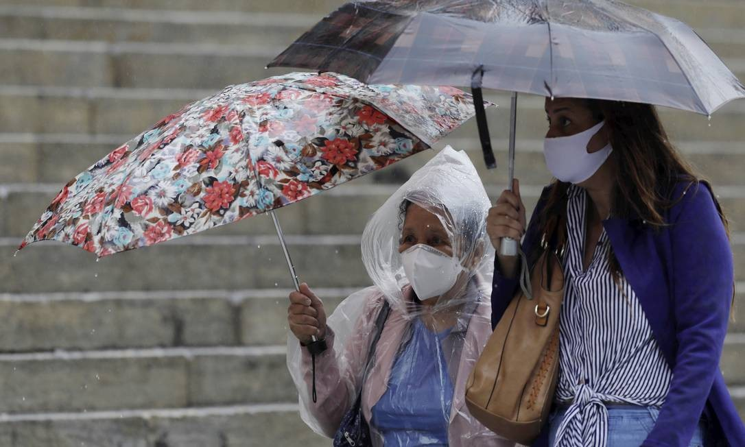 Em dia de chuva no Centro do Rio, mulheres caminham com máscara nas ruas vazias em meio o vazio causado pela pandemia. Foto: Gabriel de Paiva / Agência O Globo