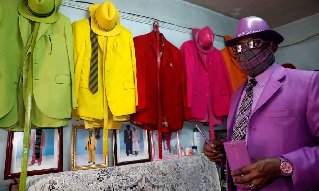 """""""Os homens sabiam usar roupas em preto, marrom, cinza ou azul escuro. Essas eram as cores dos homens """", disse ele à Reuters, combinando máscara, terno e demais acessórios: """"Deus me deu sabedoria e me mostrou todas as cores diferentes que posso usar para serem diferentes de todos os outros"""", completou Foto: THOMAS MUKOYA / REUTERS"""