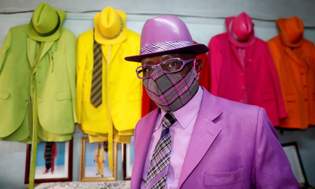 O fashionista queniano James Maina Mwangi, de 59 anos, posa para uma fotografia enquanto exibe coleção com mais de 160 ternos com acessórios a condizer, incluindo uma máscara para prevenir a infecção pela doença por coronavírus (COVID-19) em sua residência em Nairobi Foto: THOMAS MUKOYA / REUTERS