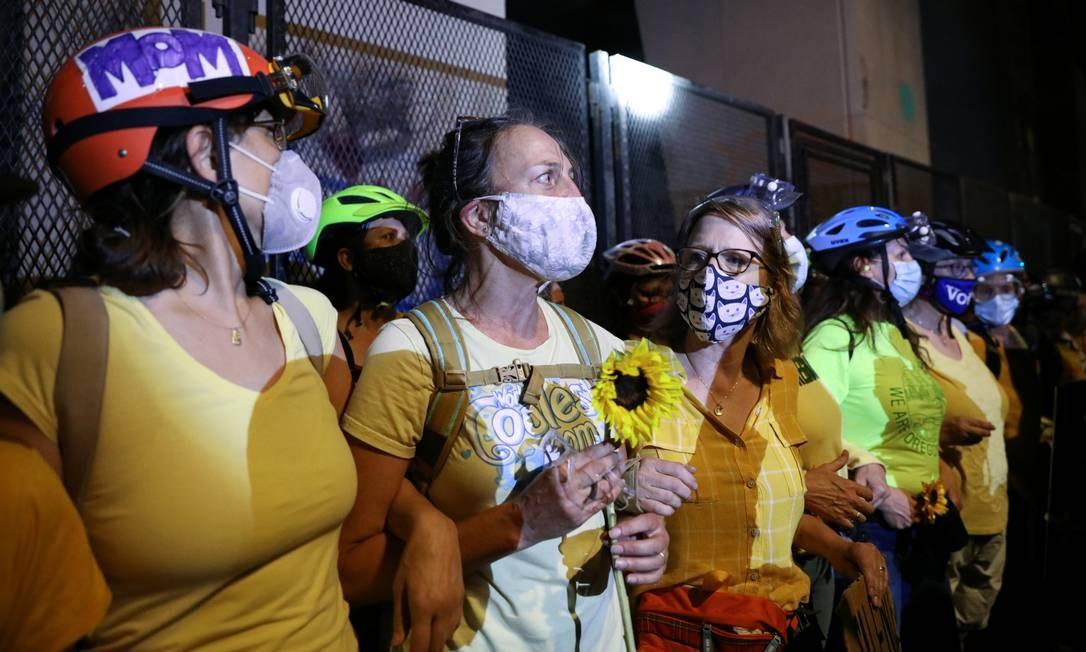 Mães ficam entre policiais e manifestantes federais durante um protesto contra a desigualdade racial em Portland, em 19 de julho Foto: CAITLIN OCHS / REUTERS
