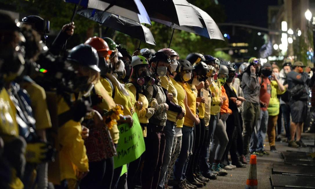Mães fazem barreira humana para proteger manifestantes durante protesto em Portland, na noite de 23 de julho. Algumas usam respiradores, máscaras de gás e capacetes Foto: ANKUR DHOLAKIA / AFP