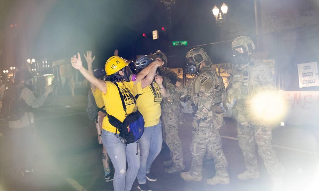 As mães ativistas formam uma barricada humana entre manifestantes e agentes federais Foto: CAITLIN OCHS / REUTERS
