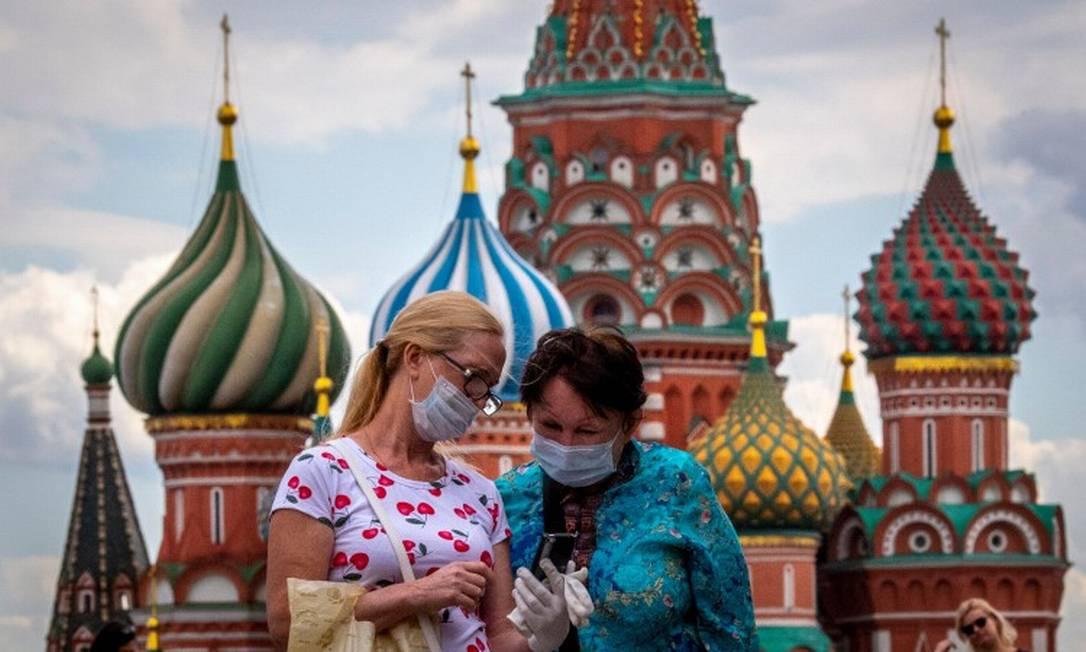 Mulheres usam máscara diante da Catedral de São Basílio Foto: YURI KADOBNOV / AFP