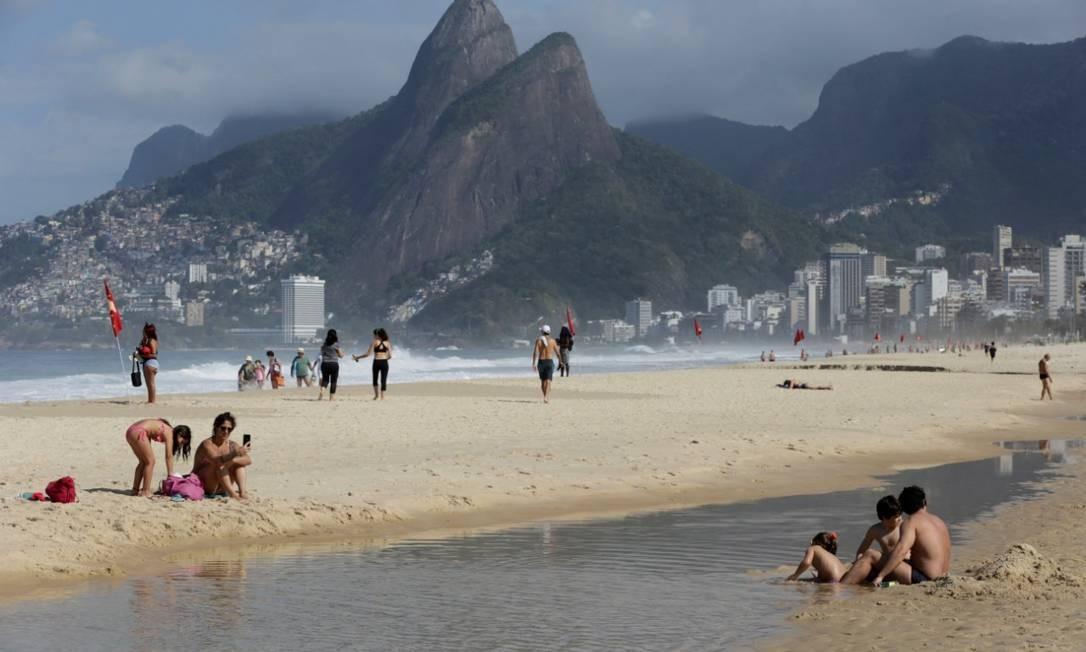 Banhistas aproveitam a praia mesmo sem a permissão para ficar na areia Foto: Domingos Peixoto