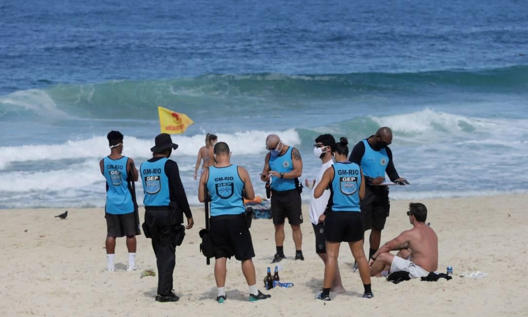 Guarda Municipal multa dois paulistas que estavam na areia sem máscara Foto: Domingos Peixoto