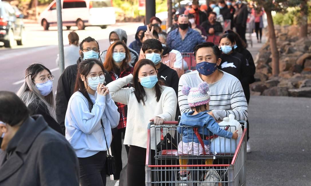 Moradores aguardam em longa fila para fazer compras em Melbourne, com anúncio de novas e mais duras restrições de deslocamento contra coronavírus Foto: WILLIAM WEST / AFP