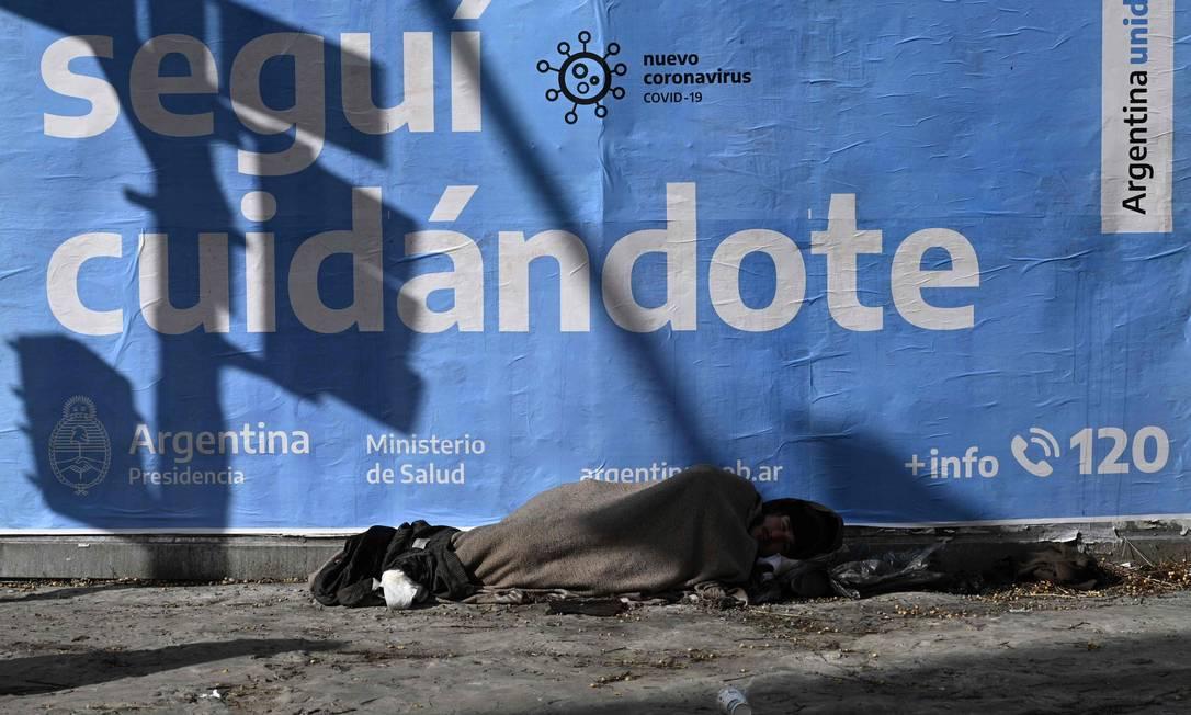 Em Buenos Aires, homem dorme na rua em frente a um cartaz de alerta sobre o coronavírus: ainda que a Argentina tenha menos casos e mortes que vizinhos, flexibilização da quarentena aumentou contágios Foto: JUAN MABROMATA / AFP/24-07-2020
