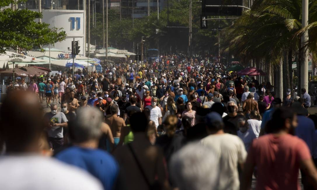 Apesar de alertas das autoridades sanitárias, cariocas e turistas não cumpriram o distanciamento mínimo para caminhar na área de lazer da Praia do Leblon: alguns passeavam com as máscaras penduradas no pescoço Foto: Márcia Foletto / Agência O Globo