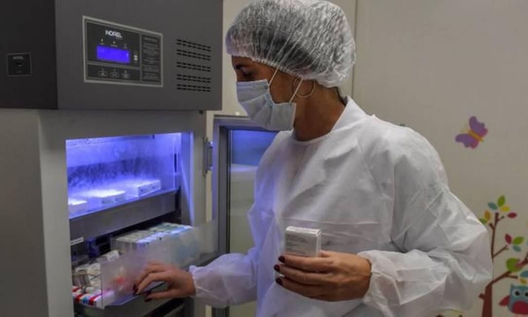 Tecnico aramazena doses de vacina em refrigerador em laboratóriol Foto: Getty Images
