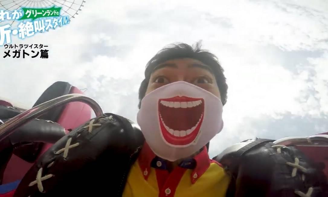 Funcionário do parque de diversões Greenland, na cidade japonesa de Kumatomo, anda de montanha-russa com um adesivo que simula um sorriso em sua máscara Foto: Reprodução