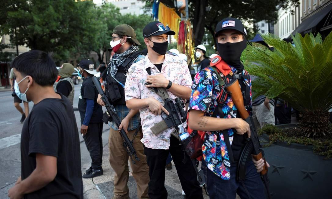 """Membro do Texas Guerrillas que se autodenomina """"Apex"""" carregam armas em um comício do Black Lives Matter em Austin, Texas, EUA. Membros dos grupos armados disseram que estavam lá para proteger o BLM e seu direito à liberdade de expressão Foto: NURI VALLBONA / REUTERS"""