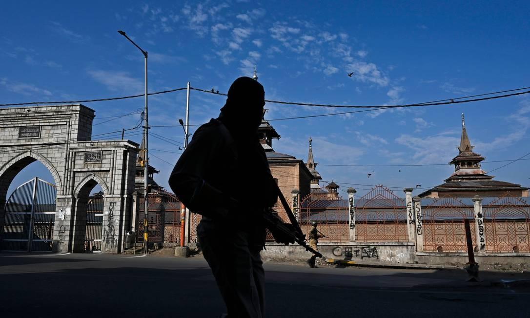 Soldados paramilitares patrulham ao longo de uma rua durante o toque de recolher em Srinagar. Um toque de recolher foi imposto na Caxemira indiana apenas dois dias antes do primeiro aniversário da abolição de Nova Déli Foto: TAUSEEF MUSTAFA / AFP