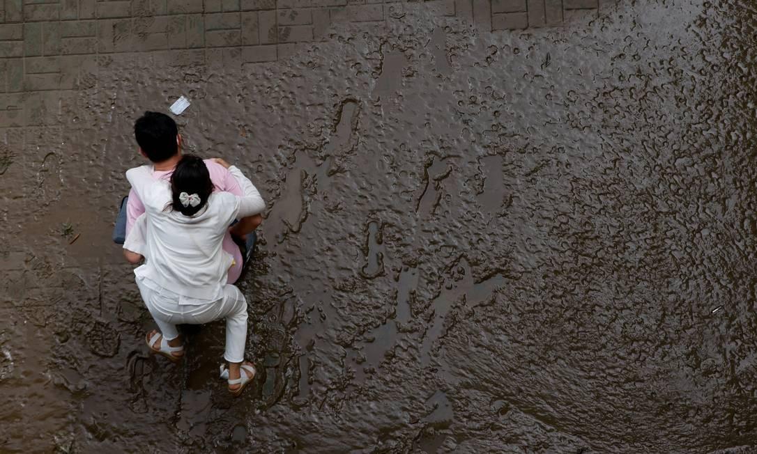 Um homem atravessa uma trilha coberta de lama carregando sua esposa nas costas em um parque inundado do rio Han em Seul, Coreia do Sul Foto: KIM HONG-JI / REUTERS