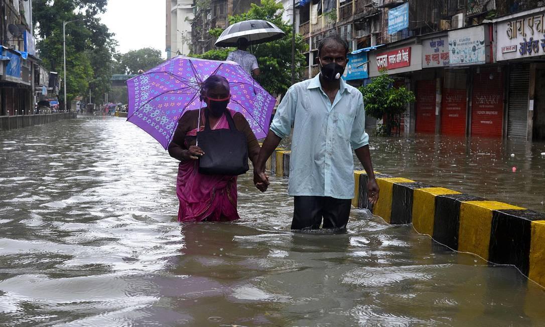 Idosos caminham com água até os joelhos ao longo de uma estrada inundada durante uma forte chuva de monções, em Mumbai, na Índia Foto: SUJIT JAISWAL / AFP