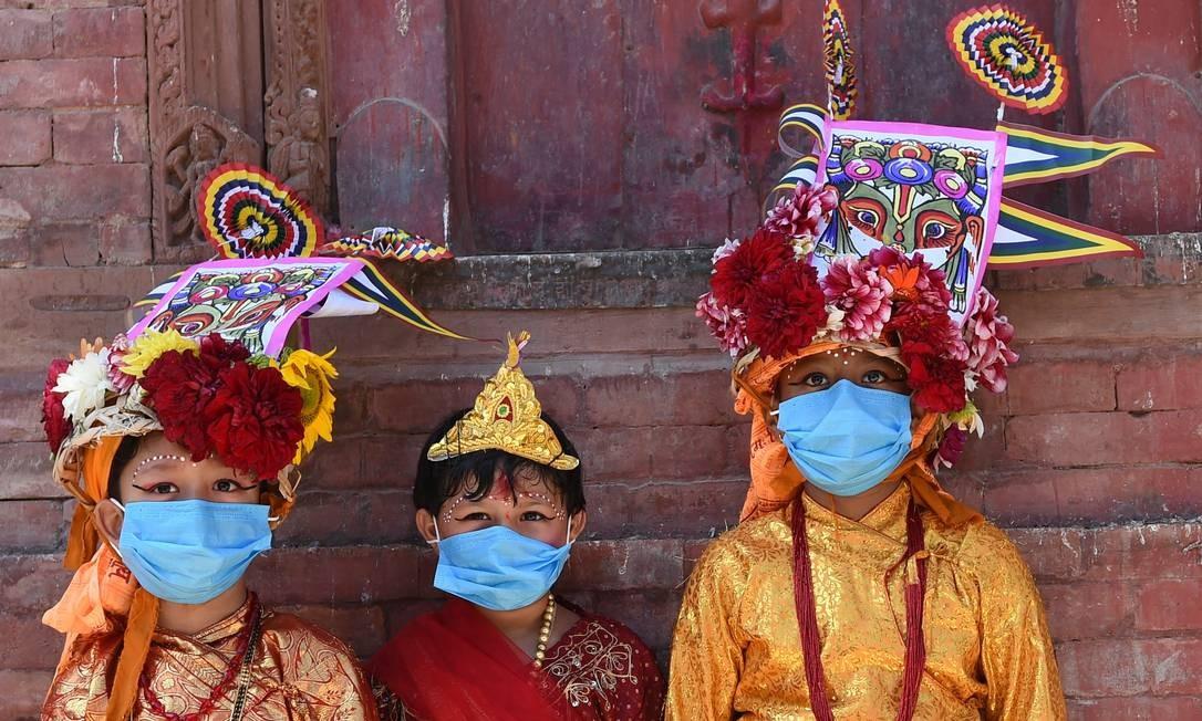 Crianças usando máscaras de proteção vestem traje tradicional de vaca para participar de uma procissão para o festival de vacas Gai Jatra em Katmandu. O festival anual de Gai Jatra, que remonta ao século XVII, é uma homenagem para aqueles que morreram no ano passado, com famílias realizando procissões coloridas pelos centros das cidades do Nepal Foto: PRAKASH MATHEMA / AFP
