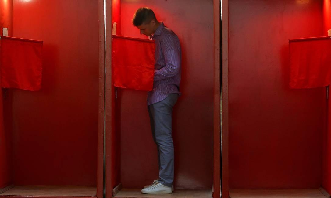 Um homem fica dentro de uma cabine de votação durante a votação antecipada, antes das eleições presidenciais de 9 de agosto, em uma assembleia de voto em Minsk, Bielorrússia Foto: VASILY FEDOSENKO / REUTERS