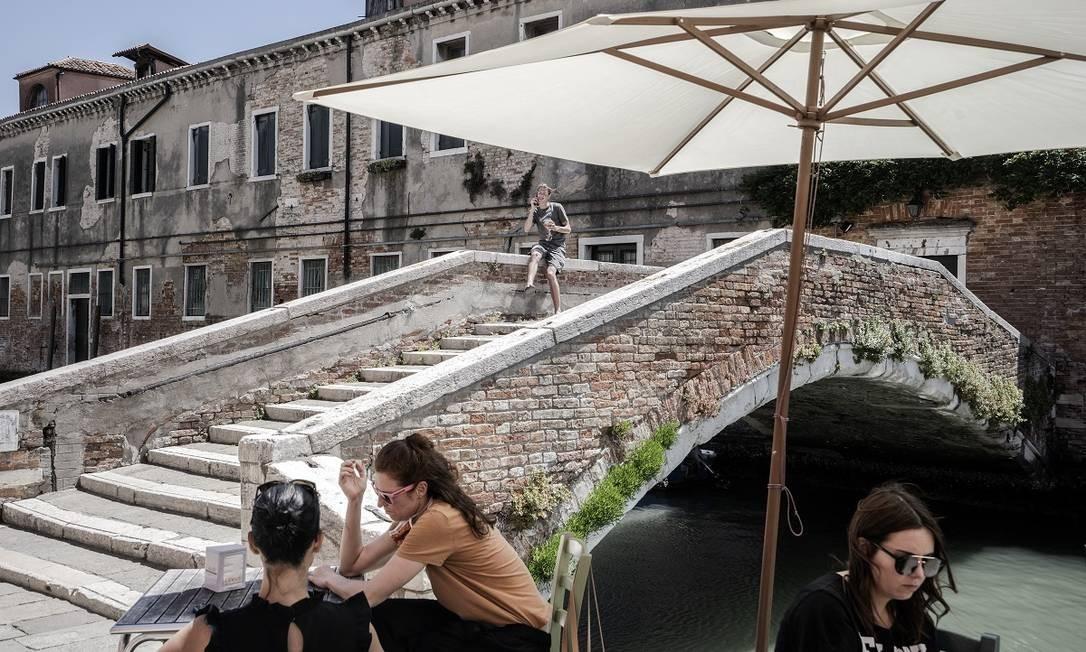 Visitantes às margens de um dos canais de Veneza, no momento em que o turismo começava a ser retomado na cidade Foto: Alessandro Grassani / The New York Times
