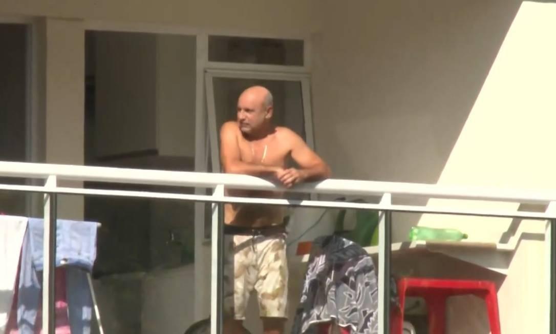 Queiroz pega sol na sacada do apartamento onde cumpre prisão domiciliar, no Rio Foto: Reprodução / Agência O Globo