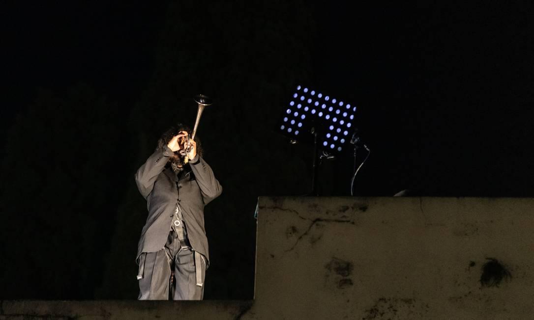 No final da performance, um músico executou o Hino Nacional de trás para frente em cima do portão de entrada do Cemitério da Consolação Foto: Matheus Maria José / Divulgação