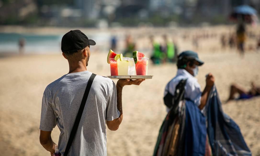 Ambulante vendendo bebidas alcóolicas na praia de Ipanema, o que está proibido pelas novas regras de combate à Covid-19 Foto: Hermes de Paula / Agência O Globo