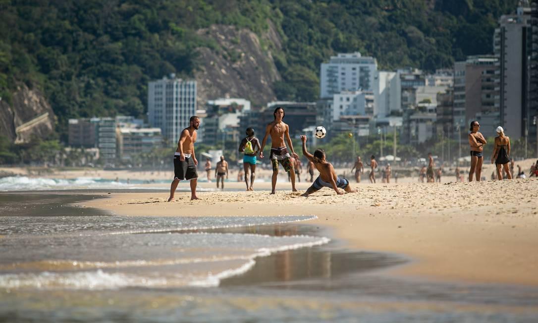 Vários grupos de três ou quatro pessoas jovagam altinha nas praias de Ipanema e Leblon nesta sexta-feira ensolarada de inverno. Prática ainda não foi liberada pela prefeitura Foto: Hermes de Paula / Agência O Globo