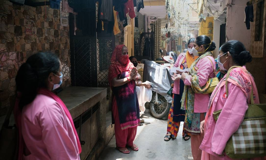 Ashas usando máscaras de proteção conversam com moradora enquanto fazem pesquisa de porta em porta sobre o coronavírus em Nova Délhi Foto: T. Narayan / Bloomberg/02-07-2020